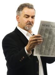 Mature man reads newspaper with serious look on face
