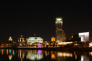 Night city. Business center in river.