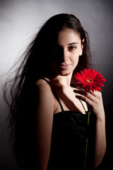 Attractive woman with red flower