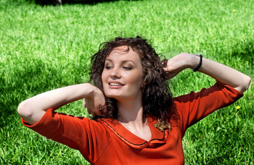 young woman stretches in grass