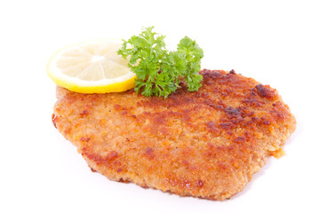 a breaded wiener schnitzel with lemon and parsley isolated over