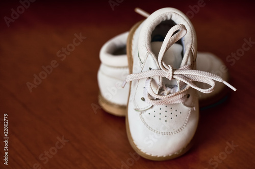 pair of white leather baby shoes with brown wood background