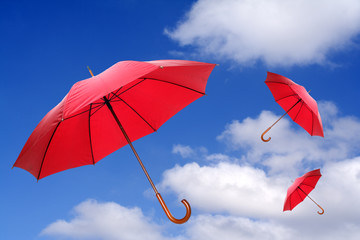 Three red umbrellas flying in a rich blue sky.