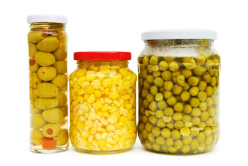 Various pickles in the glass jars on white