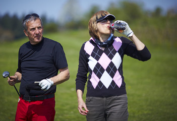 Golf couple sharing a drink on the golf course.