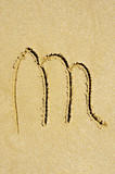 m letter written in the sand on a beach