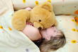 The girl sleeps with a toy bear