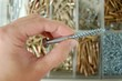 Hand mit Schraube vor Sortierkasten