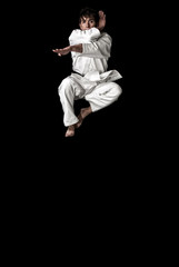 High Contrast karate young male fighter jump on black