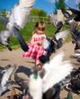 Cute little girl dress feeding pigeons