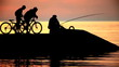Silhouettes of the fisherman and two cyclists at sunset