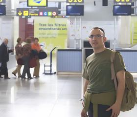 Joven frente a puertas de embarque de aeropuerto