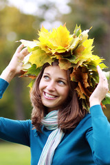 Beautiful woman with diadem made from yellow maple leaves .