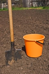 orange bucket and shovel on a field