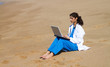 indian doctor using laptop on beach