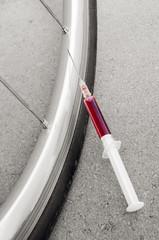 Doping syringe at road bike racing wheel