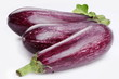 Purple eggplants with leaves on white background