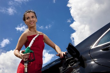 Woman with fuel nozzle on gas station with black car