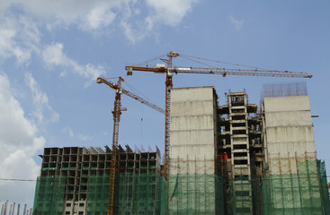 Two construction cranes working on a commercial building
