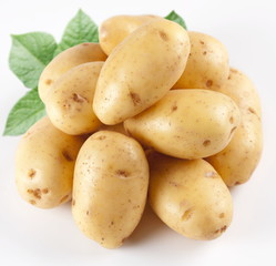 Yellow potatoes with leaves on a white background