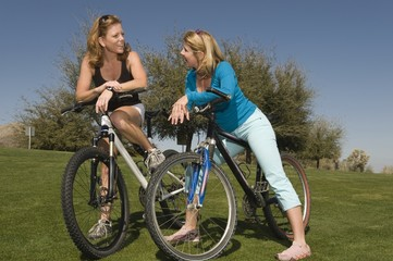 Two friends lean on their bikes talking