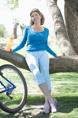 Mature woman leans on tree with her bike