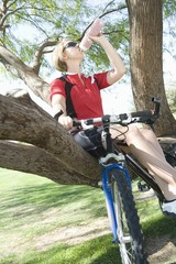 Mid adult cyclist drinking water on a tree with her bike