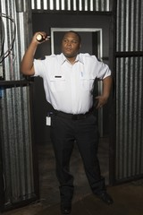 Security guard stands at corrugated metal doorway with torch