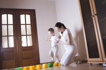 Boy walks along building blocks with help from his mother