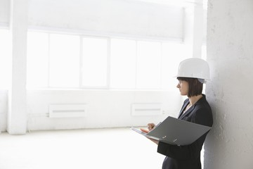Business woman with file in empty warehouse