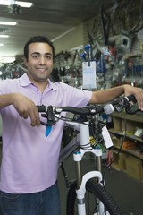 Bike shop assistant stands holding new bike