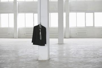 Suit jacket hangs on pillar in empty warehouse