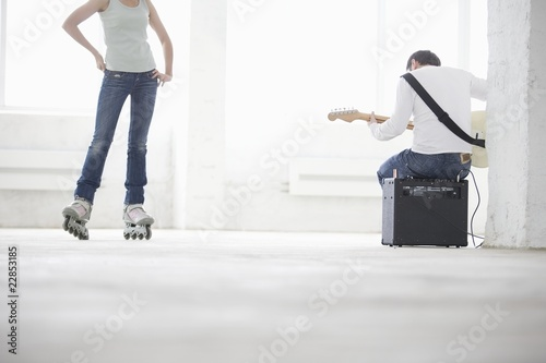 Woman on roller skates and man sitting on amp playing electric guitar