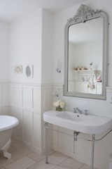 Grey painted mirror surround in panelled bathroom, London
