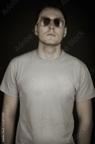 Mid adult man stands in sunglasses