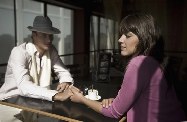 Young couple sit holding hands in cafe