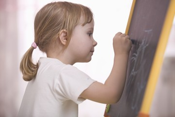Young girl drawing on chalkboard