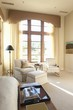 Sunlit floor to ceiling windows in cream living room interior