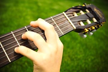 closeup of a boys hand with a guitar