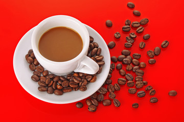 Small white cup of coffee with coffee grain on red background