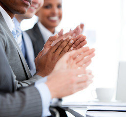 Close up of a  mixed business team applauding a presentation