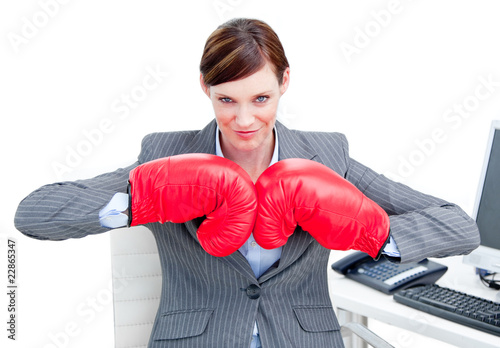 Confident businesswoman preparing to fight with boxing gloves