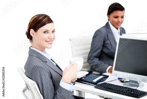 Smiling female business partners having a break drinking coffee