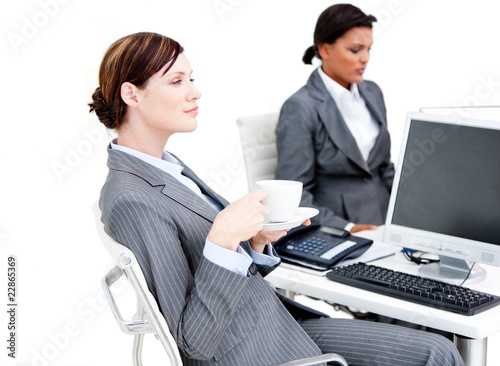 Busy female business partners having a break drinking coffee