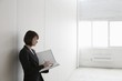 Business woman stands with file in empty warehouse