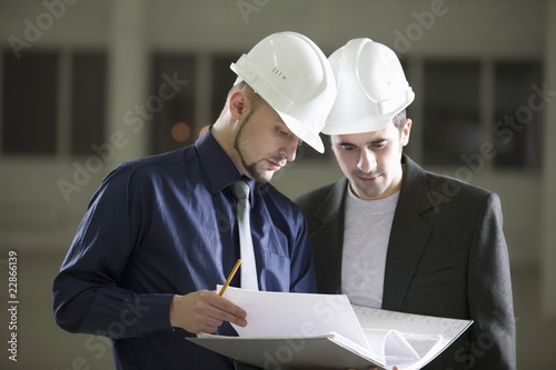 Two colleagues consult file documentation