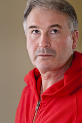 Mature man in red sweater with look of determination