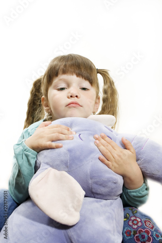 Little girl cuddling a stuffed elephant