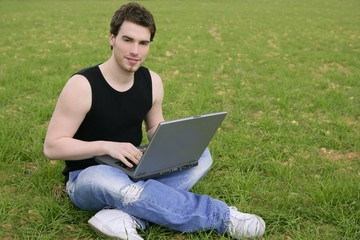 student young man laptop computer on meadow