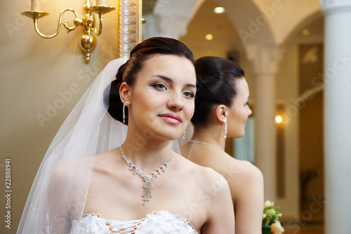 Beautiful bride near mirror in wedding palace